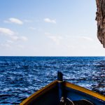 boat leaving blue grotto cave in malta