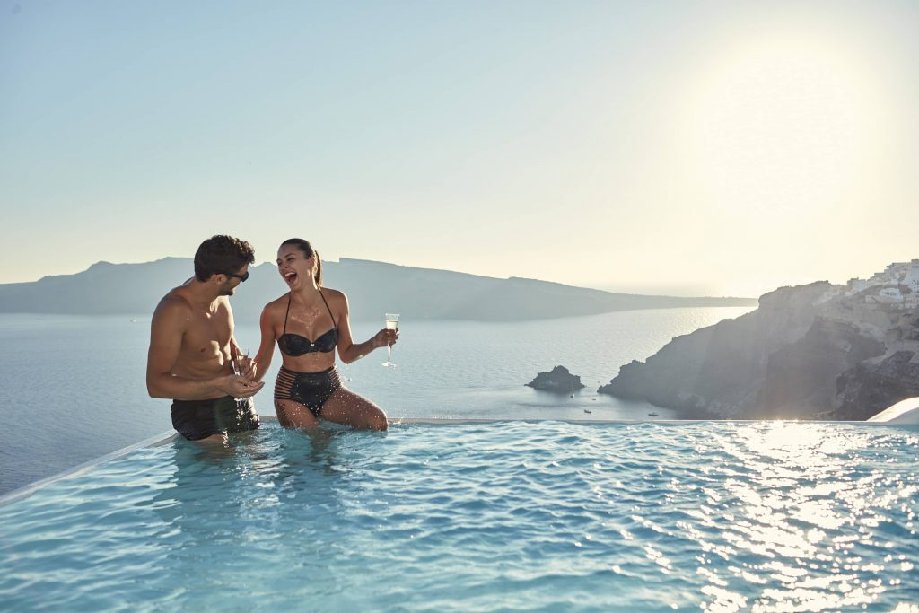 couple at the Canaves Oia Suites Infinity Pool in Santorini
