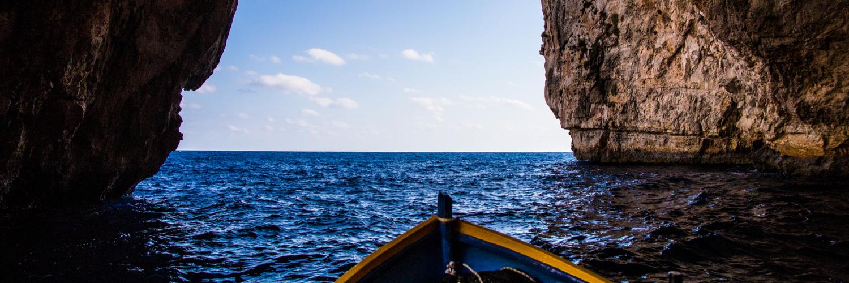 boat leaving blue grotto cave in malta